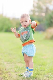 Junge kratzt sich am rücken von einem mückenstich, während er auf einem grünen rasen steht. ein insektenstich.