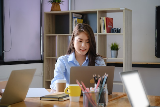 Junge kreative asiatische geschäftsfrau, die im büro trifft und inhalt auf laptop fokussiert. brainstorming arbeitsgruppe konzept.