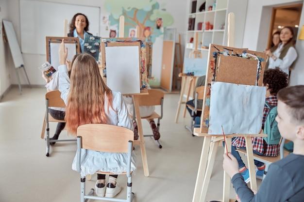 Junge kreative glückliche schüler im hellen modernen klassenzimmer machen zeichenstunde