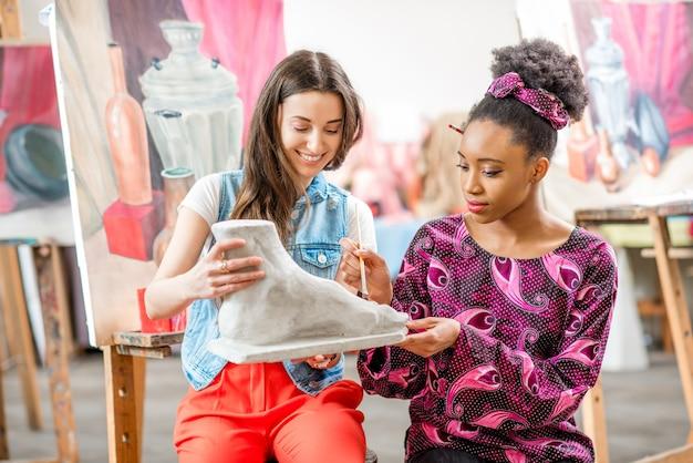 Junge kreative multiethnische studenten, die den gipsfuß im universitätsstudio zum malen betrachten