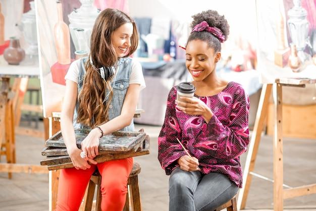 Junge kreative multiethnizität-studenten sitzen während der pause im uni-atelier zum malen