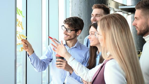 Junge kreative startup-geschäftsleute, die sich in modernen büros treffen, planen projekte mit postaufklebern auf glas.