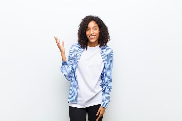 Junge kühle afroamerikanische frau, die glücklich, überrascht und fröhlich fühlt, mit positiver einstellung lächelt, eine lösung oder idee realisierend