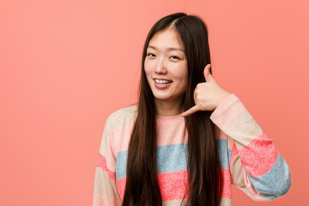 Junge kühle chinesische frau, die eine handyanrufgeste mit den fingern zeigt.