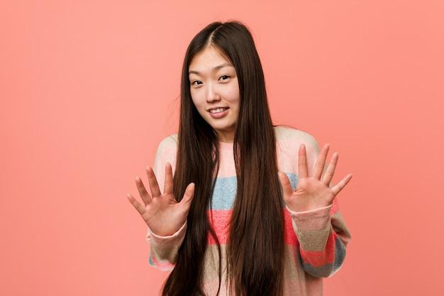Junge kühle chinesische frau, die jemand zeigt eine geste des ekels zurückweist.