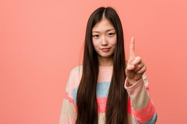 Junge kühle chinesische frau, die nummer eins mit dem finger zeigt.