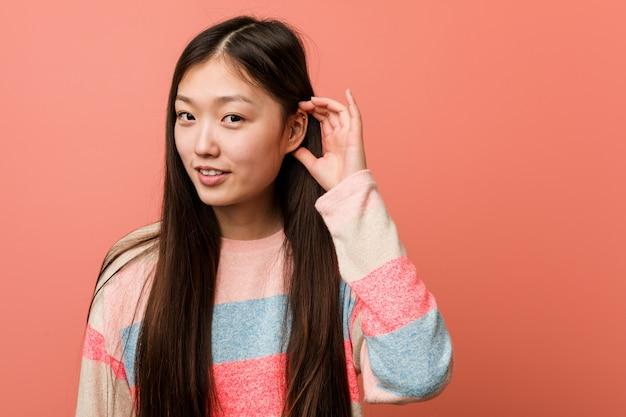 Junge kühle chinesische frau, die zum hören eines klatsches versucht.