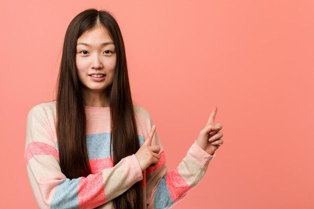 Junge kühle chinesische frau entsetzte das zeigen mit den zeigefingern auf einen kopienraum.