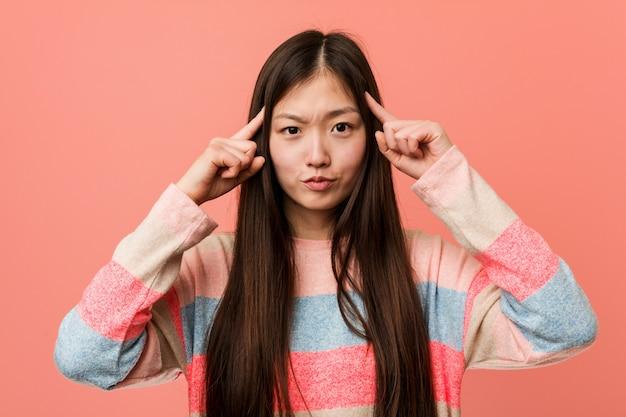 Junge kühle chinesische frau konzentrierte sich auf eine aufgabe und hielt ihn die zeigefinger, die kopf zeigen.