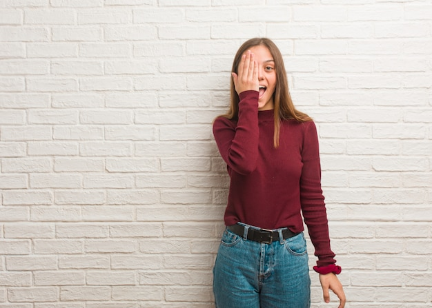 Junge kühle frau über einer ziegelsteinwand, die glückliches und bedeckungsgesicht mit der hand schreit