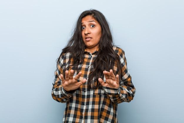 Junge kühle indische frau, die jemand zeigt eine geste des ekels zurückweist.