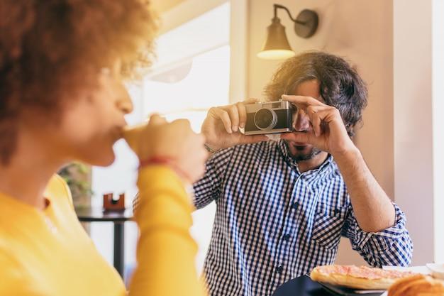 Junge kühle paare, die am café frühstücken er macht ihr ein foto mit einer vintage-kamera.