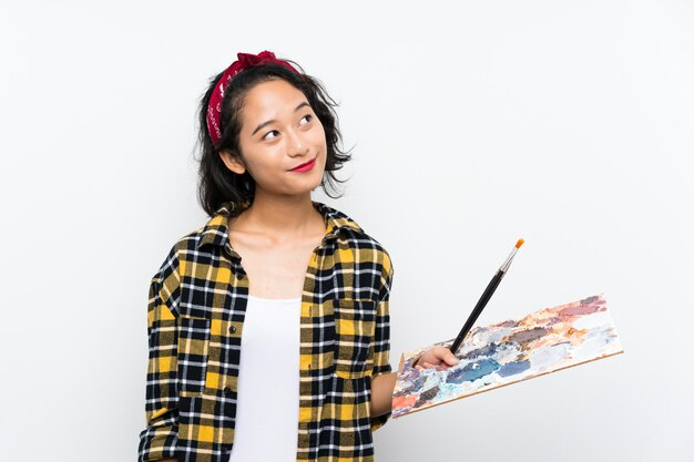 Junge künstlerfrau, die eine palette über der lokalisierten weißen wand oben schaut beim lächeln hält
