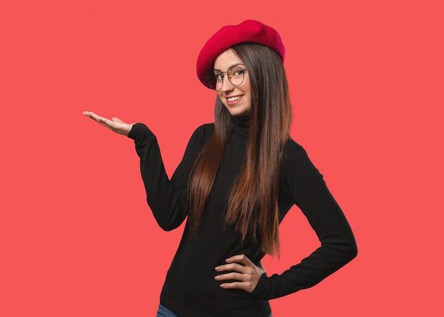 Junge künstlerfrau, die etwas mit der hand hält