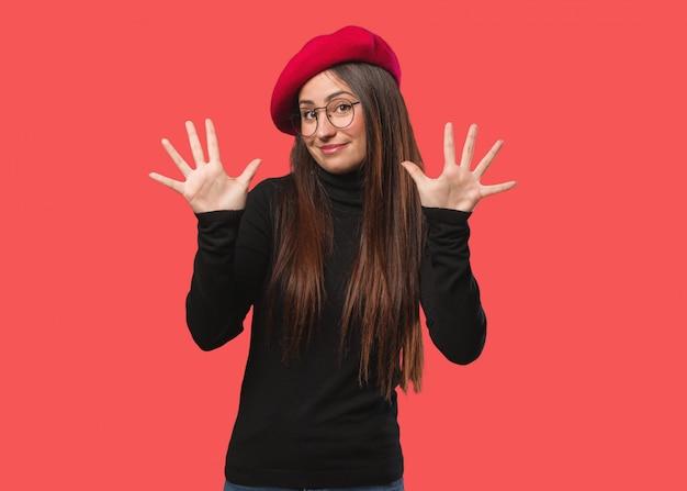 Junge künstlerfrau, die nr. zehn zeigt