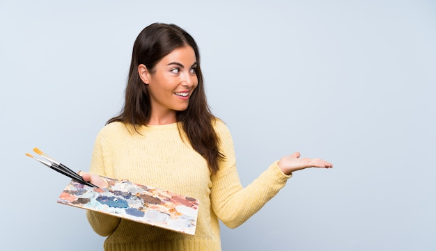 Junge künstlerfrau über lokalisierter blauer wand mit überraschungsgesichtsausdruck