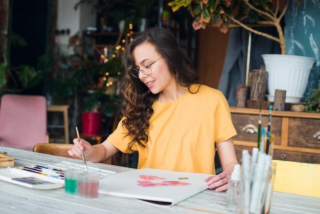 Junge künstlerin, die an ihrem arbeitsplatz skizziert