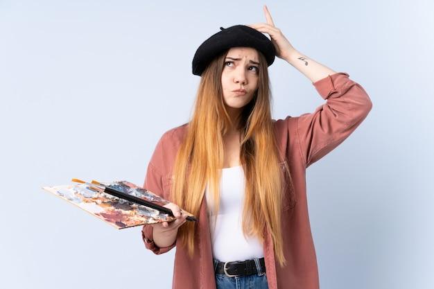 Junge künstlerin, die eine palette auf blauer wand hält, die zweifel und mit verwirrendem gesichtsausdruck hat