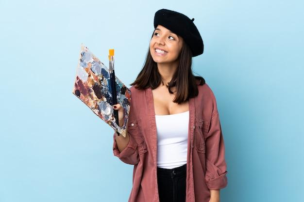 Junge künstlerin, die eine palette auf lokalisiertem blau hält, das eine idee beim nachschlagen denkt