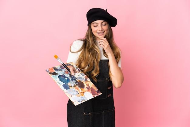 Junge künstlerin, die eine palette lokalisiert auf rosa hält, die zur seite schaut und lächelt