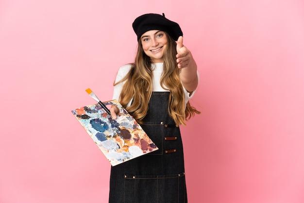 Junge künstlerin, die eine palette lokalisiert auf rosa händeschütteln für das schließen eines guten geschäfts hält