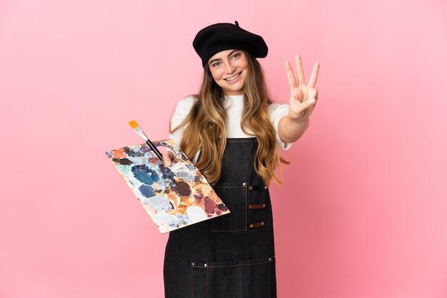 Junge künstlerin, die eine palette lokalisiert auf rosa wand glücklich hält und drei mit den fingern zählt