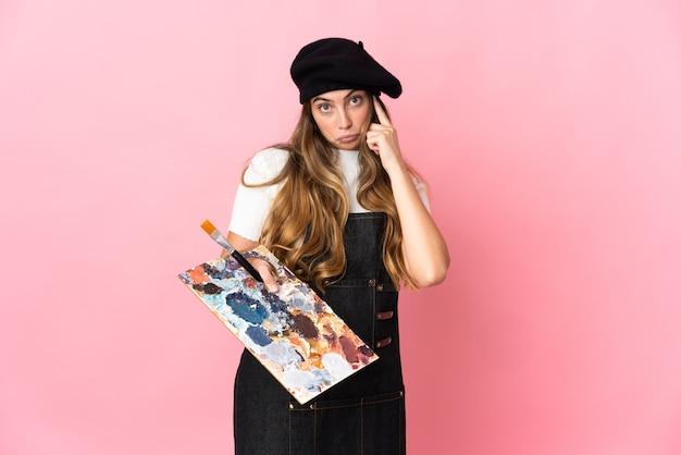 Junge künstlerin, die eine palette lokalisiert auf rosa wand hält, die eine idee denkt