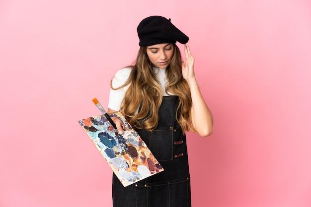 Junge künstlerin, die eine palette lokalisiert auf rosa wand mit kopfschmerzen hält