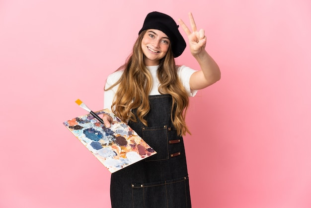 Junge künstlerin, die eine palette lokalisiert auf rosa wandlächeln und siegeszeichen zeigend hält