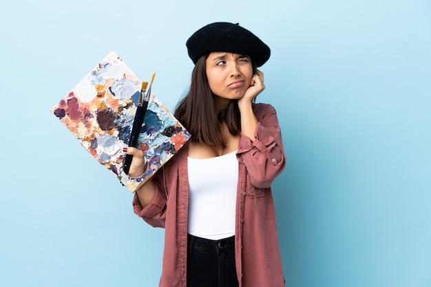 Junge künstlerin, die eine palette über isolierte blaue wand hält, frustriert und ohren bedeckend