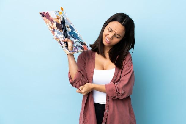 Junge künstlerin, die eine palette über isoliertem blau mit schmerz im ellbogen hält.