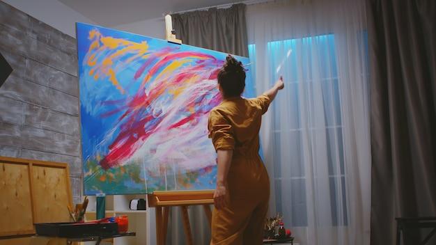 Junge künstlerin, die ihre bunte abstrakte malerei betrachtet.