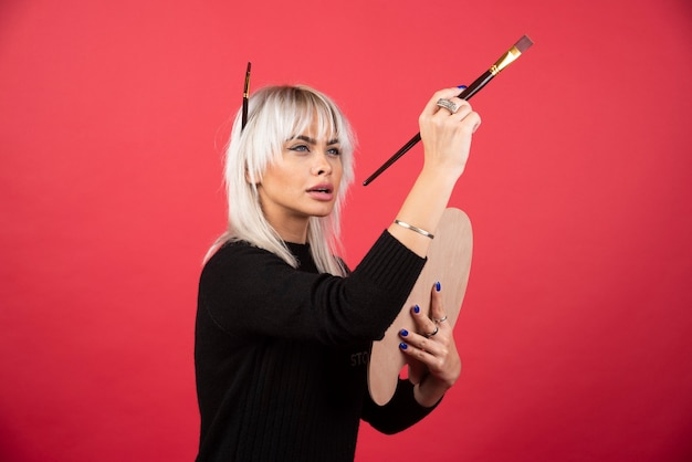 Junge künstlerin, die kunstvorräte an einer roten wand hält.