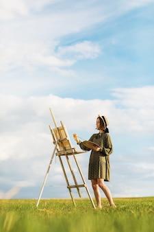 Junge künstlerin malt ein bild im freien an einem warmen sommerabend