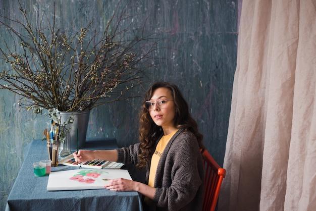 Junge künstlerin oder designerin arbeiten in ihrem atelier