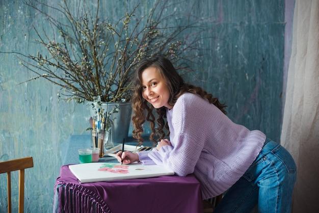 Junge künstlerin oder designerin, die an ihrem arbeitsplatz skizziert