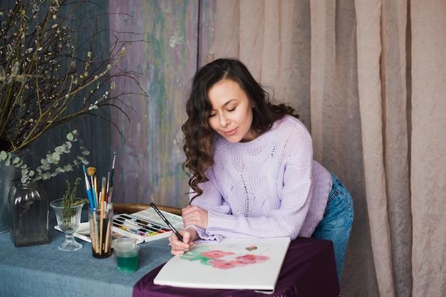 Junge künstlerin oder designerin, die in ihrem studio skizziert