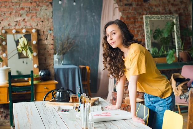 Junge künstlerin posiert in ihrem studio