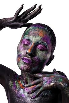 Junge künstlerische frau in der schwarzen farbe und im bunten pulver. glühendes dunkles make-up. kreative körperkunst zum thema raum und sterne. bodypainting-projekt: kunst, schönheit, mode.