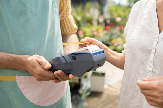 Junge kundin des gartencenters, die für ihren kauf mit kreditkarte bezahlt, während sie ihn über dem zahlungsautomaten hält