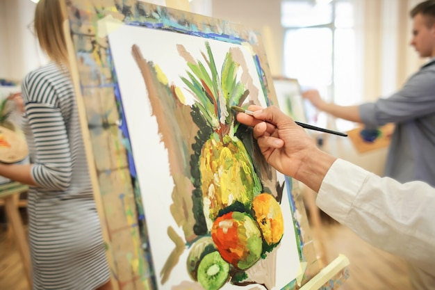 Junge kunststudentin malt stillleben in werkstatt