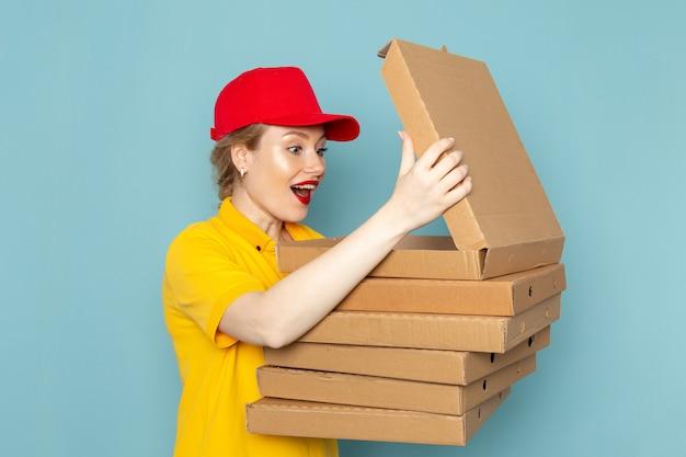 Junge kurierin der vorderansicht im gelben hemd und im roten umhang, der pakete hält, die sie auf dem blauen raumarbeiter öffnen
