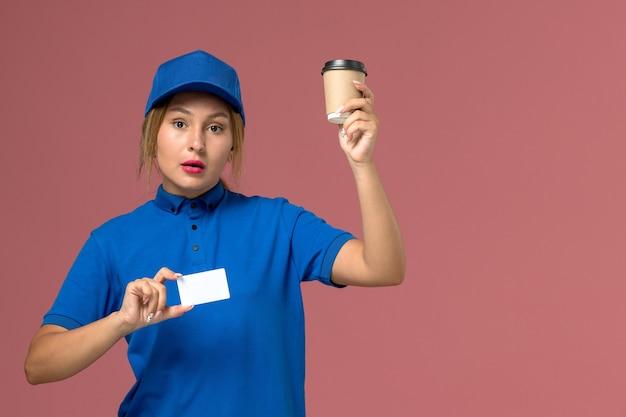 Junge kurierin der vorderansicht in der blauen uniform, die das halten der braunen lieferschale des kaffees aufstellt, dienstuniform-lieferfrau-jobarbeiter
