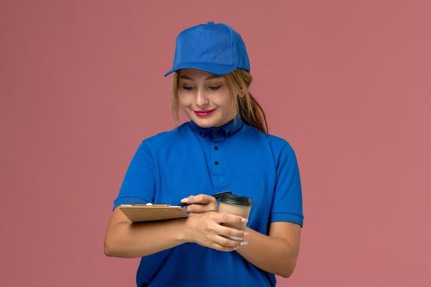Junge kurierin der vorderansicht in der blauen uniform, die das halten der tasse kaffee und des notizblocks aufstellt, dienstuniformenlieferungsarbeiterin