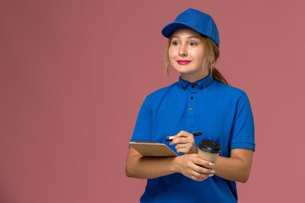 Junge kurierin der vorderansicht in der blauen uniform, die das halten der tasse kaffee und des notizblocks mit leichtem lächeln aufwirft, dienstuniformenlieferungsarbeiterin