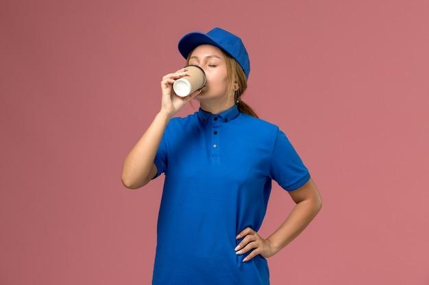Junge kurierin der vorderansicht in der blauen uniform, die deivery kaffee auf der rosa wand, dienstjobuniform-lieferfrau aufwirft und trinkt