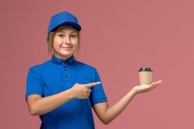 Junge kurierin der vorderansicht in der blauen uniform, die die auslieferungsschale des kaffees mit lächeln auf der rosa wand aufwirft und hält, dienstjobuniformauslieferungsfrau