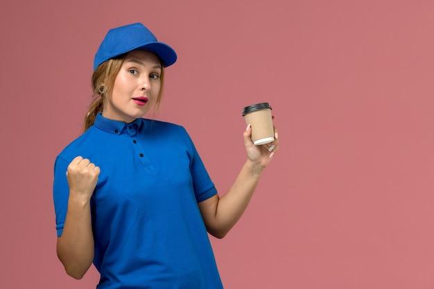 Junge kurierin der vorderansicht in der blauen uniform, die die braune lieferschale des kaffees auf der rosa wand aufstellt, dienstjobuniformlieferfrau