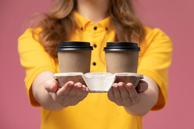 Junge kurierin der vorderansicht in der gelben uniform, die braune kaffeetassen aus kunststoff auf dunkelrosa hintergrundjobuniform-lieferfarbdienstarbeiter hält