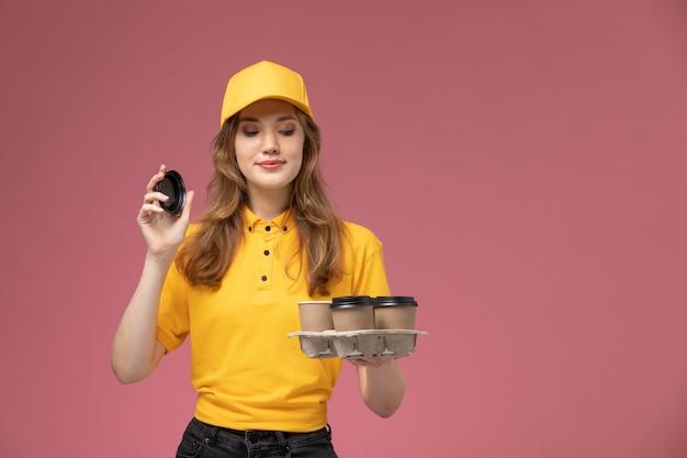 Junge kurierin der vorderansicht in der gelben uniform, die braune kaffeetassen des plastiks braun auf dem rosa hintergrundjobuniformlieferfarbdienstarbeiter hält